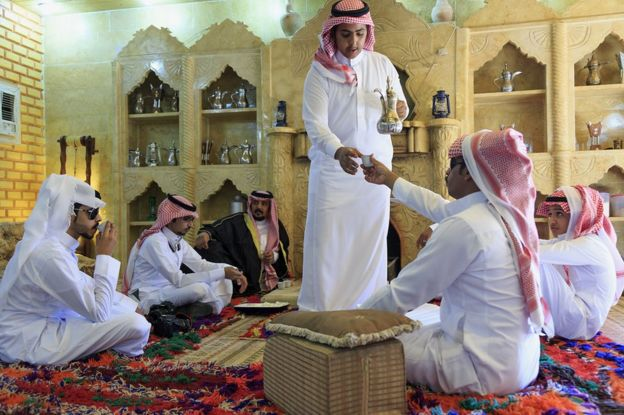Saudi Muslim men drink Arabic coffee as they celebrate the first day of Eid al-Fitr at in Tabuk, some 1,500 kilometres northwest of the Saudi capital Riyadh near the border with Jordan, on 17 July 2015
