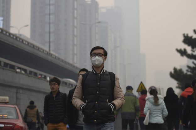 A man wearing a face mask walks along the street on a hazy day in Shenyang in northeastern China's Liaoning province Monday, 9 November 2015.