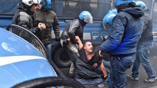 در این تصویر یک تظاهراتکننده دیده میشود که از سوی ماموران پلیس احاطه شده و در حالی که روی زمین افتاده ماموران بازوهای او را گرفتهاند و به نظر میرسد در برابر ماموران مقاومت میکند