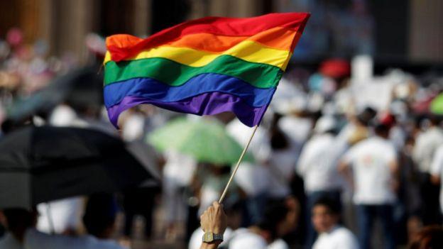Un hombre sostiene una bandera de la comunidad LGBT en Monterrey, durante las marchas en contra del matrimonio gay.