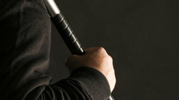 Homem segura bastão