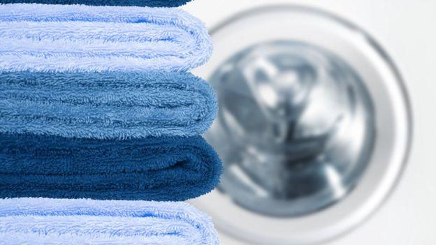 Pila de toallas con lavarropas de fondo