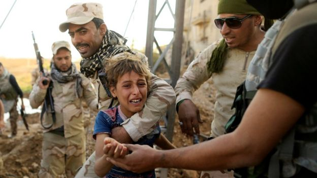 Iraqi soldiers help a child flee the front line in Mosul. 4 Nov 2016