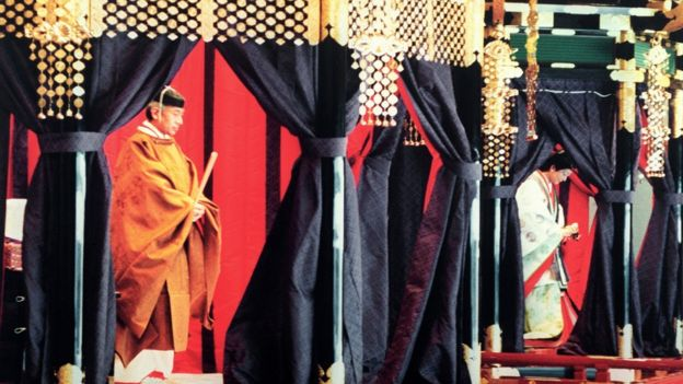 Emperor Akihito (L), wearing a traditional Japanese costume, stands inside the Takamikura (Imperial throne) during the enthronement ceremony at the Imperial Palace - to the right Empress Michiko - 12 November 1990