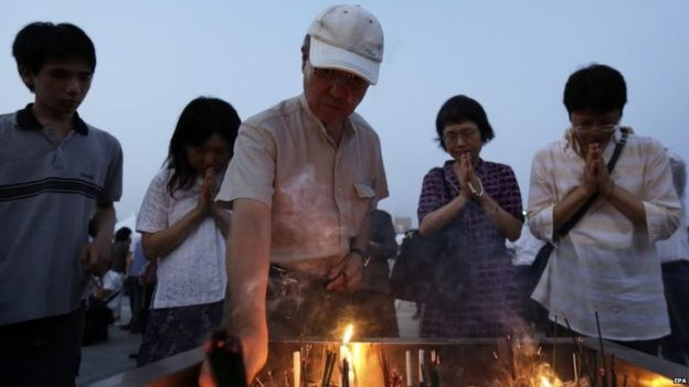 A man lights an incense stick while others offer prayers for victims of the atomic bombing during World War Two in Hiroshima (06 August 2015)