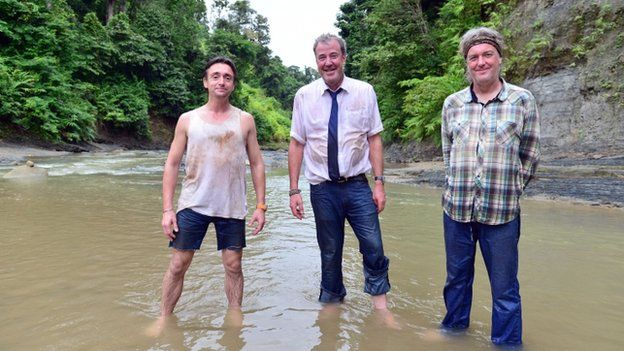Richard Hammond, Jeremy Clarkson and James May stood in a muddy river
