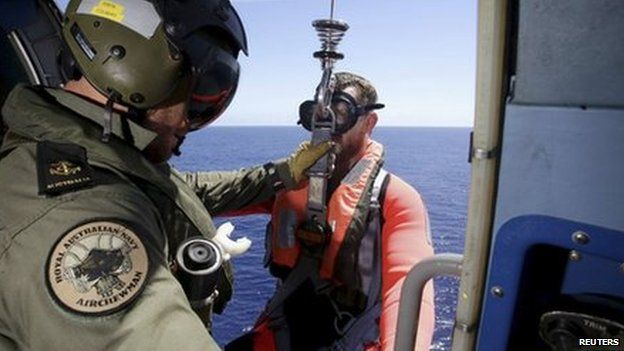 A search team member is lowered into the Indian Ocean to retrieve possible debris