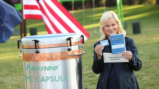 Amy Poehler as Leslie Knope, standing next to an American flag and a time capsule