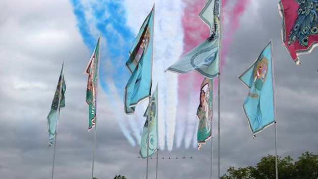 Red Arrows fly past flags
