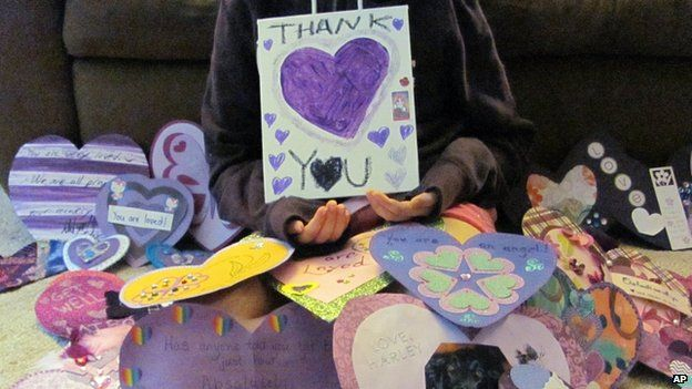 A girl holds a thank you poster in Waukesha, Wisconsin, on 19 June 2014