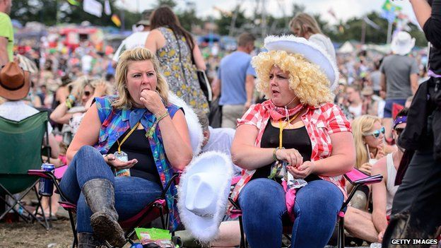 Two of the thousands of Dolly Parton fans waiting to see their idol perform her Glastonbury debut