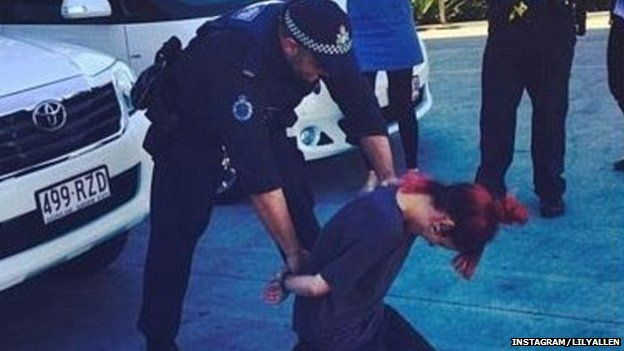Police officer putting handcuffs on Lily Allen