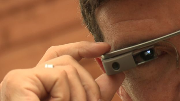 A close up of man wearing the Google Glass. The glass screen goes directly across his eye and his is pressing a button on the top of the glass