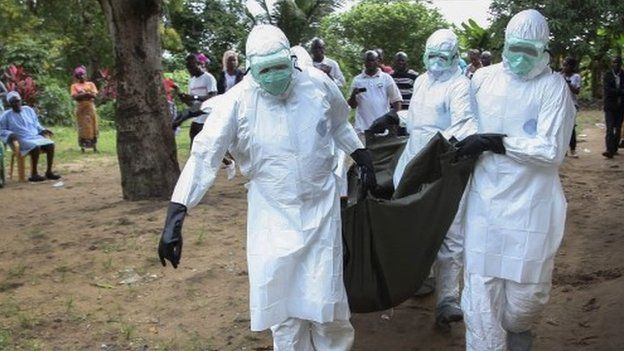Liberian nurses carry the body of an Ebola victim from a home in the Banjor Community on the outskirts of Monrovia, Liberia - 6 August 2014