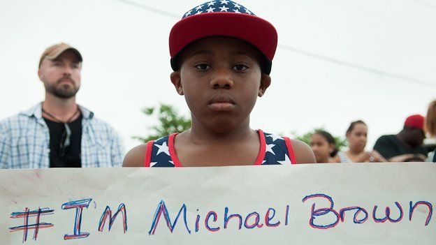 "A protestor stands outside a church in Ferguson, Missouri, holding a sign reading ""I'm Michael Brown"""