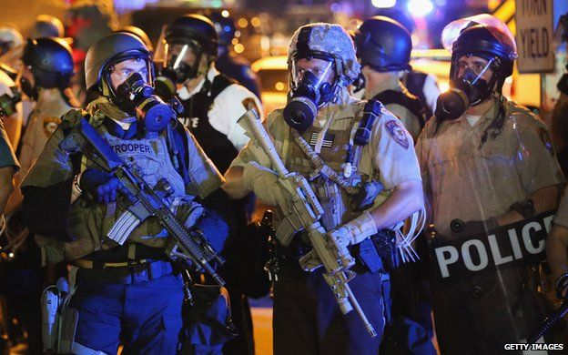 Police wearing gas masks and holding guns
