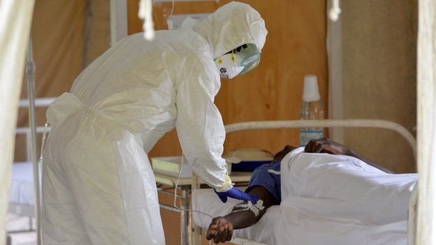 A health worker in protective gear and an ebola patient