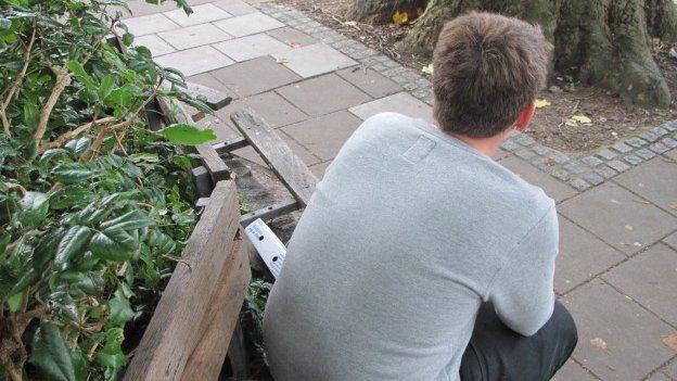 Matt sitting on a bench facing away