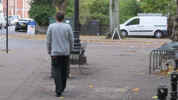 Matt walking away down a street