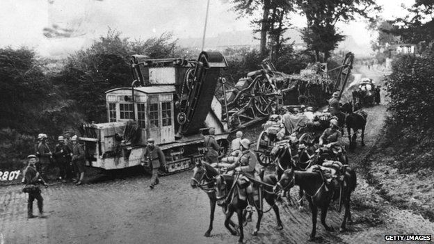 German troops manoeuvre a trench cutter along a country road.