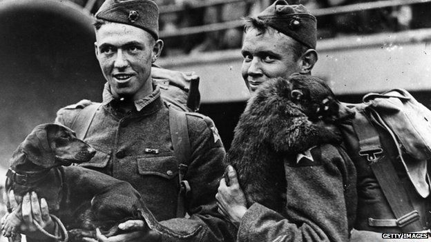 Two American soldiers about to embark for duty, with their pets, a dachshund and a racoon.