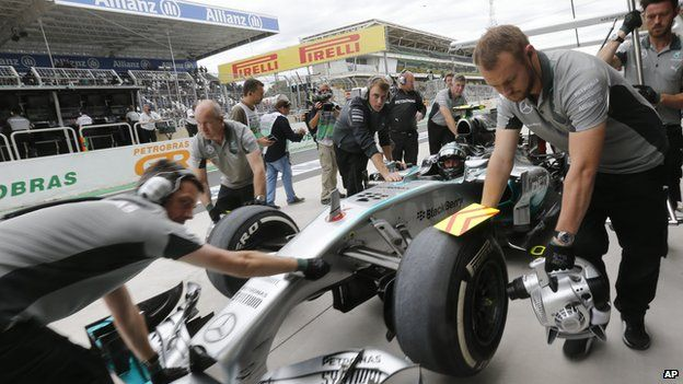 Formula 1 engineers change the wheels on a car