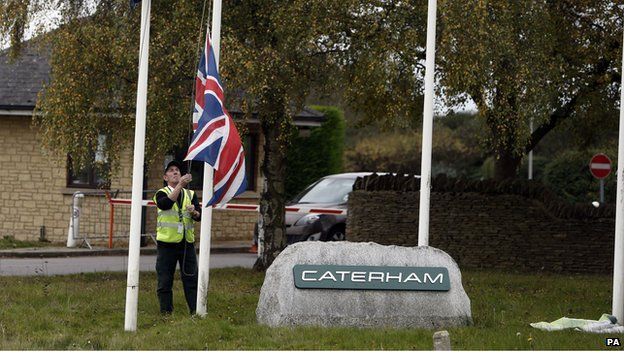 A man removes the Union flag at Caterham's headquarters