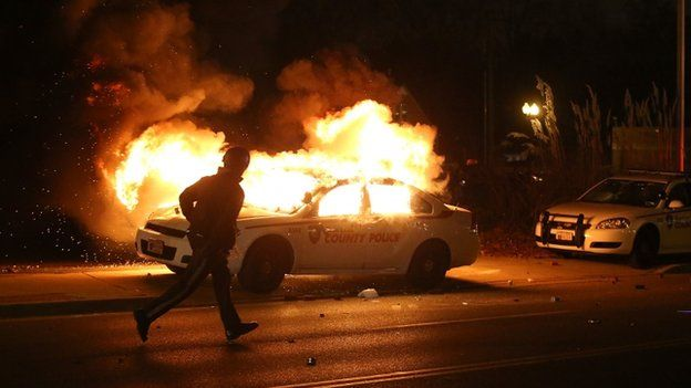 A police officer runs by a burning police car during a demonstration on 24 November 2014 in Ferguson, Missouri.