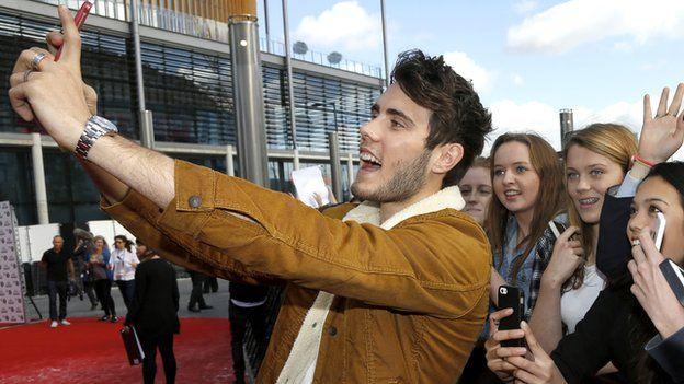 Alfie Deyes taking a selfie with fans