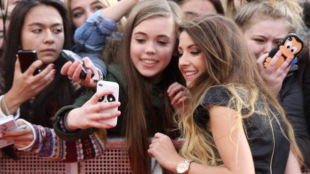 Zoella taking a selfie with fans
