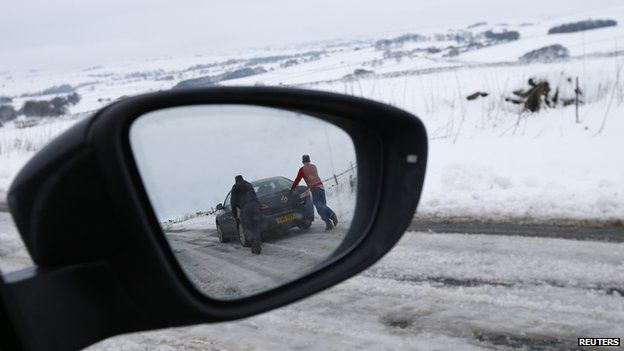 Men pushing a car reflected in a wing mirror