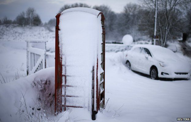 Phone box and car covered in snow