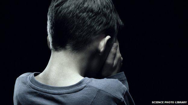 A young boy hiding his face