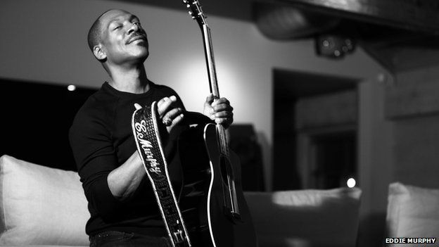 Eddie Murphy poses with a guitar