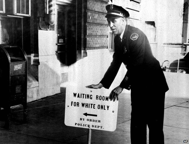 "Policeman with a sign reading: ""Waiting room for white only by order police dept."""