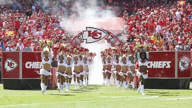 Cheerleaders coming out on to the field in front of a crowd
