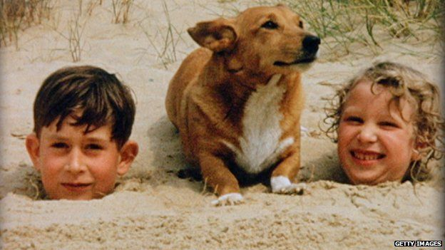 A young Prince Charles and Princess Anne play with a corgi as children