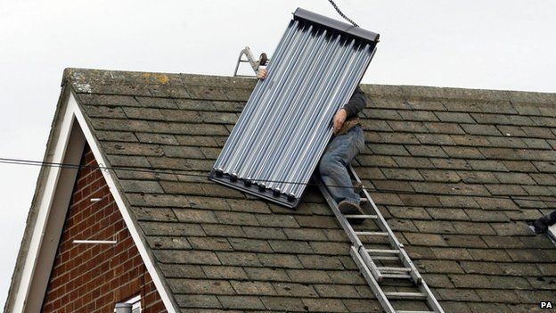 Man putting solar panels on a roof