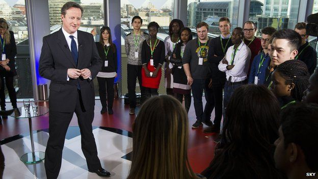 David Cameron standing in front of a group of young people