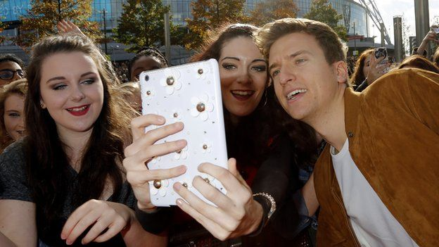 Greg James taking a selfie with fans