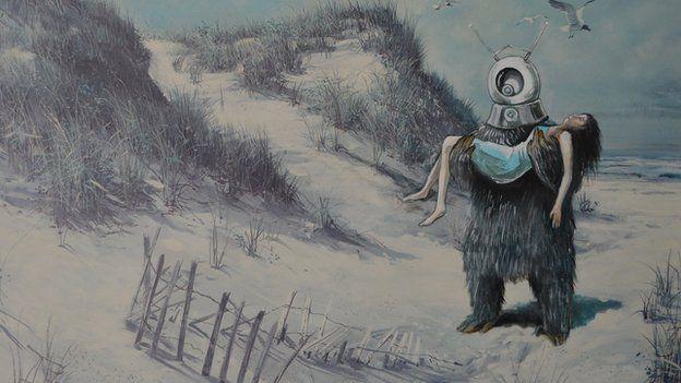 An alien holds a woman, walking through sand dunes on a beach