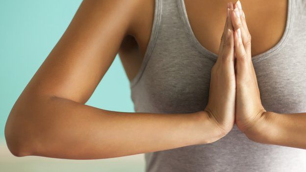 Someone doing yoga with hands together in prayer
