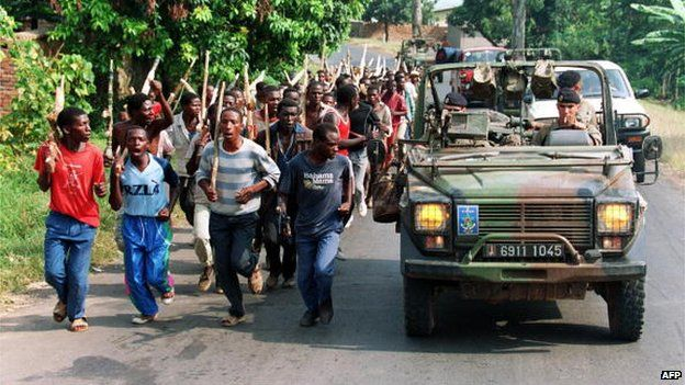 French troops driving past Hutu militiamen