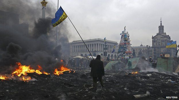 Manifestant anti-gouvernement en portant le drapeau national à travers Place de l'Indépendance à Kiev, Feb ici 2014.