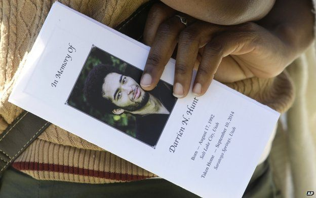 A family friend holds the funeral programme for Darrien Hunt following his funeral on 18 September 2014, in Saratoga Springs, Utah