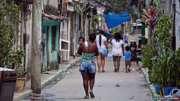 A woman carries a baby in Vila Uniao in January 2015