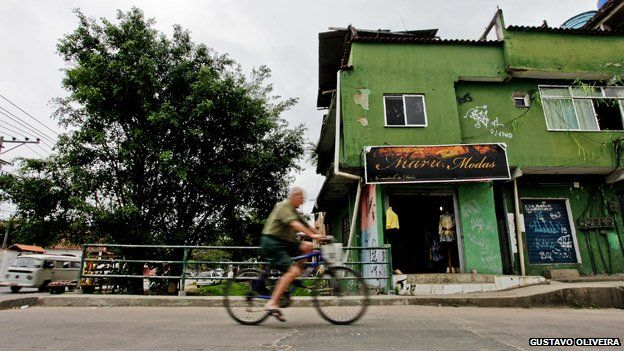 A man cycles past a shop in Vila Uniao in January 2015