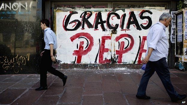 People walk past graffiti thanking Jose 'Pepe' Mujica, Uruguay's outgoing president - 28 February 2015