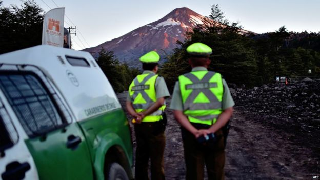 Policemen stand guard at the entrance of the road that leads to the refuge of the Villarrica volcano, near Villarrica in southern Chile