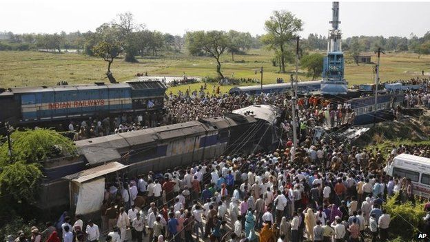 Rescue workers and others gather at the site of a train accident near Bachhrawan village in the northern Indian state of Uttar Pradesh, Friday, 20 March 2015.